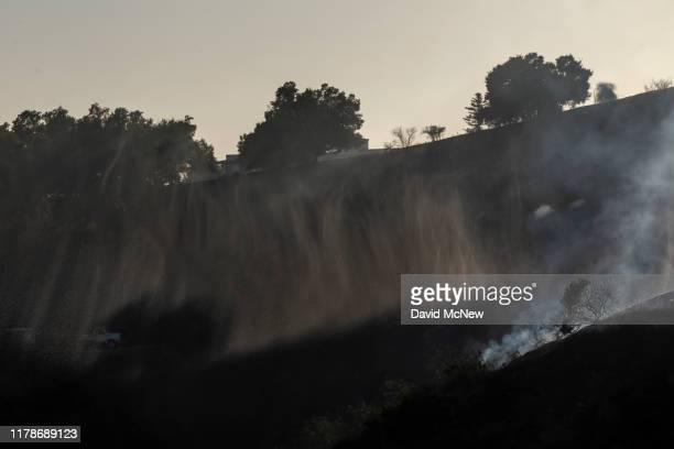 The final mist of water dropped from a firefighting helicopter falls over the Getty Fire on October 28 2019 in Los Angeles California Reported at 130...