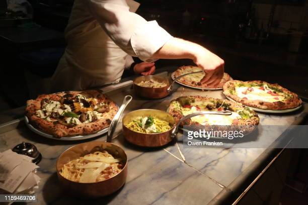 the final preparation of foods before being picked up by the servers, in an italian restaurant in paris - image stock pictures, royalty-free photos & images