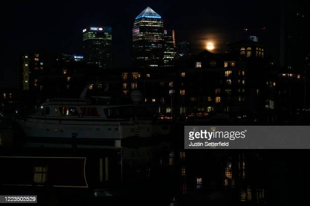 The final super moon of the year also known as the flower moon rises over Canary Wharf on May 07 2020 in London United Kingdom A supermoon occurs...