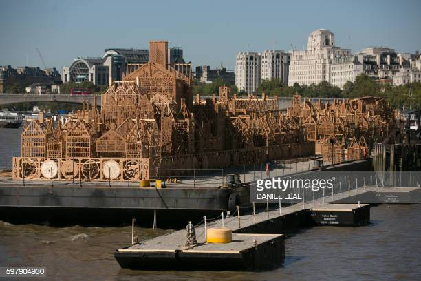 The final touches are made to a 120 metrelong wooden sculpture of London's skyline from the seventeenth century as it is moored up on the river...