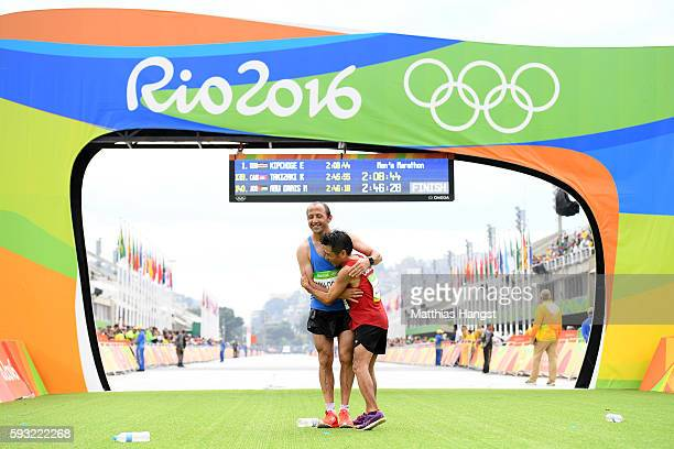 The final two finioshers Kuniaki Takizaki of Cambodia embrace Methkal Abu Drais of Jordan as they cross the finish line during the Men's Marathon on...