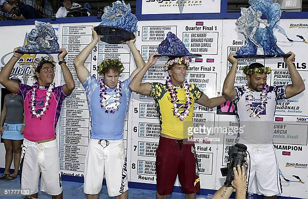 The finalists of the Vans Triple Crown of Surfing hold their trophies after the championship November 22 2004 at Ali'i Beach Park in Haleiwa Hawaii...