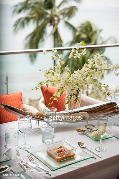 The fine dining luxuries on a table of a balcony overlooking the ocean from the Raffles hotel