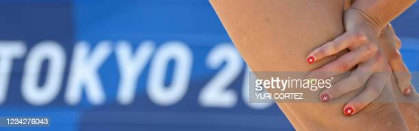 The fingernails of Switzerland's Joana Heidrich are painted with the design of the Switzerland national flag in their women's preliminary beach...