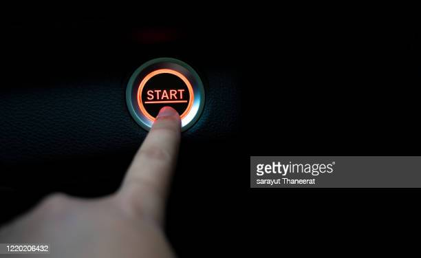 the fingers are pressing the start push button. startup concept. - anfang stock-fotos und bilder