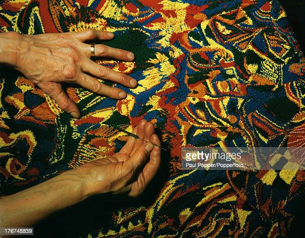 The fingers of English artist Madge Gill busy at work on an original piece of embroidery made from odd scraps of coloured wool, London, England, 19th...