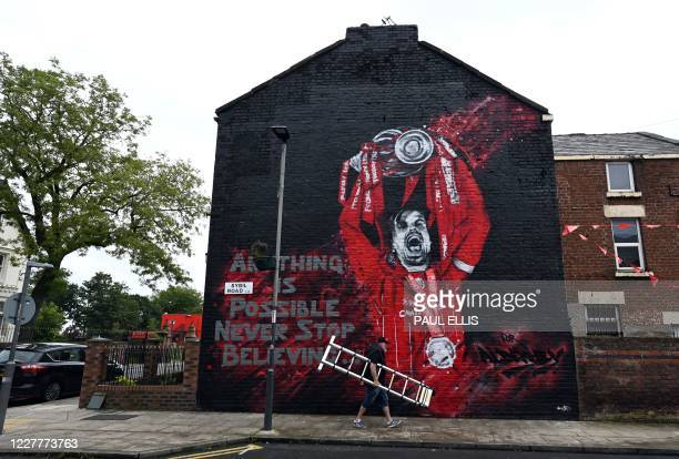 TOPSHOT The finished new mural of Liverpool's English midfielder Jordan Henderson lifting the Premier League trophy created by graffiti artists...