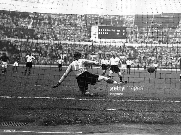 The Finnish goal keeper Olavi Laaksonen fails to prevent Austria scoring a penalty goal during a football match at the 1952 Helsinki Olympics
