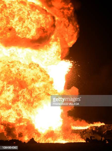 The fire is raging behind the bodies of burned victims at the scene of a massive blaze trigerred by a leaky pipeline in Tlahuelilpan Hidalgo state...