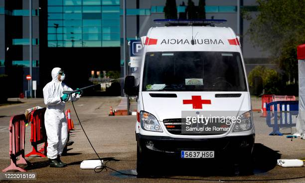 The firefighters of the IFEMA Covid-19 hospital disinfect a Red Cross ambulance on April 30, 2020 in Madrid, Spain. Since April 27 children under 12...