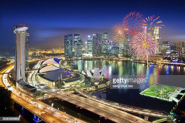 The fireworks display seem from the top of singapore flyer overlooking the whole prime central financial district building in the blue hour cityscape.