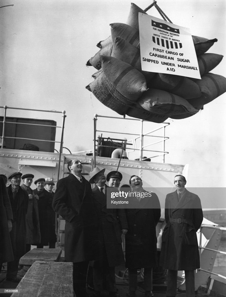 The first consignment of sugar under the Marshall Aid plan arrives at the Royal Victoria. A load is lowered on to the deck watched by officials including John Strachey (1901 - 1963), Minister of Food.