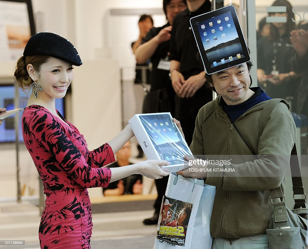 The first customer in the shop, Kazuki Miura (R), receives his iPad from fashion model, singer and actress Lena Fujii, as they start to go on sale at the shop ofJapanese internet service provider Softbank, Apple's exclusive partner in Japan, in central Tokyo on May 28, 2010. Apple's much-hyped iPad went on sale in a swathe of countries from Australia and Japan to Europe at the start of a global rollout tipped to change the face of computing.