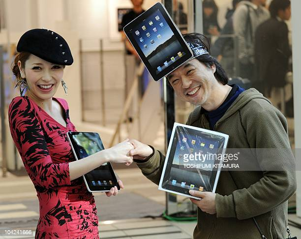 The first customer in the shop Kazuki Miura receives his iPad from fashion model singer and actress Lena Fujii as they start to go on sale at the...