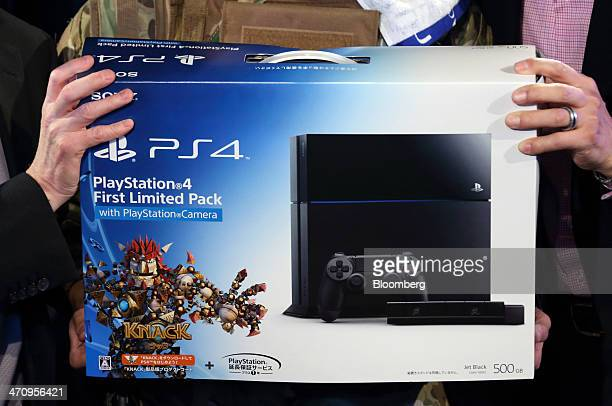 The first customer to purchase the PlayStation 4 video game console holds the box at the launch of the PS4 console at the Sony showroom in Tokyo...