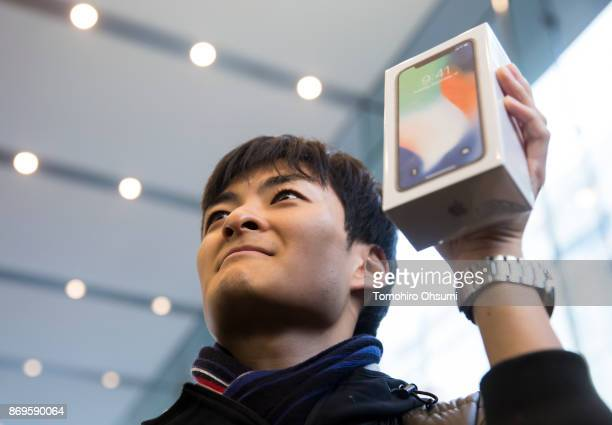 The first customer to the Apple Omotesando store holds a box containing his iPhone X as he poses to the media on November 3 2017 in Tokyo Japan Apple...