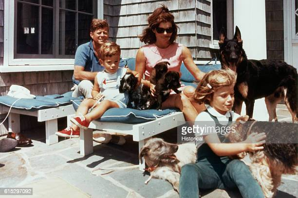 The first family on the patio of their Squaw Island House in Hyannisport Massachusetts with several puppies and dogs