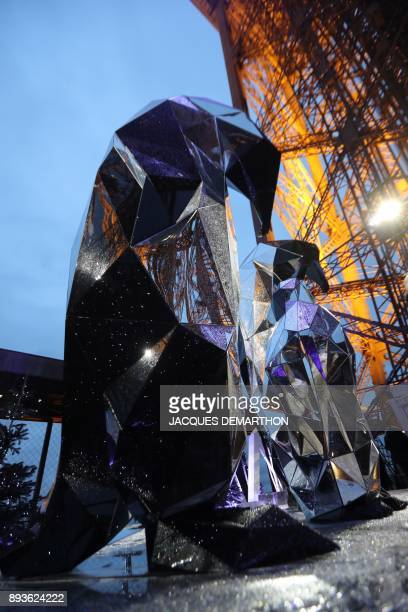 The first floor's terrace of the Eiffel Tower is decorated with snow-covered Christmas trees, sculptures of penguins, a false ice field and...
