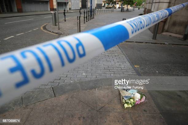 The first floral tributes to the victims of the terrorist attack are placed on the empty streets on Shudehill May 23 2017 in Manchester England An...