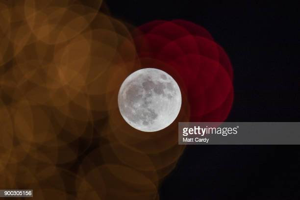 The first full moon of 2018 rises behind festive seasonal lights on display in the High Street in Wells on January 1 2018 in Somerset England...