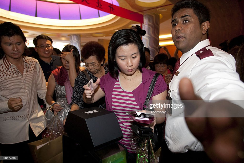 The first gamblers enter the casino at Genting Singapore Plc's Resorts World Sentosa on its first day of operation, in Singapore, on Sunday, Feb. 14, 2010. Genting Singapore Plc, the unit of Asia's largest publicly traded gambling operator, opened the country's first casino as Lunar New Year celebrations commenced. Photographer: Charles Pertwee/Bloomberg via Getty Images