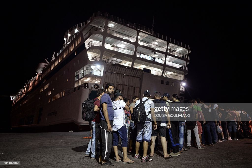 The first group of Syrian migrants wait to embark the Eleftherios Venizelos liner, which will serve as registration and accommodation center at the island of Kos early on August 16, 2015. Authorities on the island of Kos have been so overwhelmed with a surge in migrants that the government on August 14 sent a ferry to serve as a temporary centre to issue travel documents to Syrian refugees -- among some 7,000 migrants stranded on the island of about 30,000 people. Scores of exhausted migrants, many of whom arrived on inflatable boats early on August 15, were turned away from the ferry that was due to start registering new arrivals.
