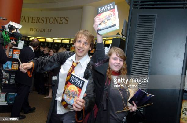 The first Harry Potter fans pose at the Waterstone's Bookstore with the final book by author JK Rowling Harry Potter and the Deathly Hallows on July...