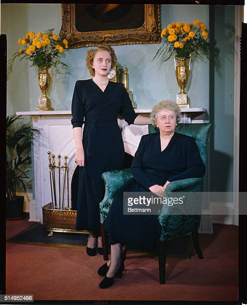 The first ladies of the land Mrs Harry S Truman and her daughter Margaret pose for a new picture in front of the fireplace at the Blair House their...