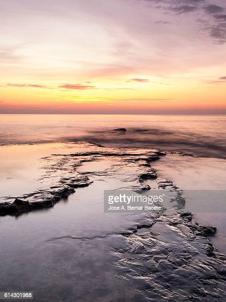 The first light of dawn colored orange beachfront in an area of coast with rocks and waves in motion
