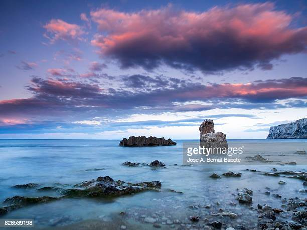 the first light of dawn colored pink beachfront in an area of coast with rocks and waves in motion - denia stock pictures, royalty-free photos & images