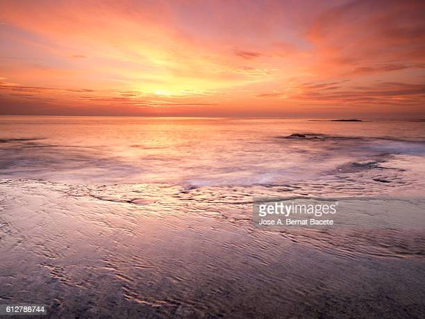 the first light of dawn orange beachfront in an area of coast with rocks and waves in motion - flowing cape stock pictures, royalty-free photos & images