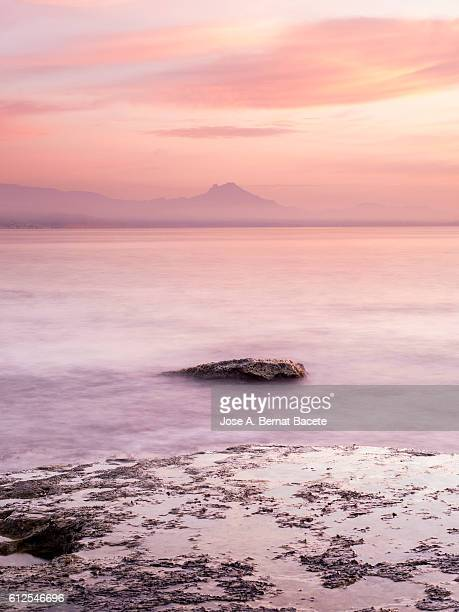 the first light of dawn pink beachfront in an area of coast with rocks and waves in motion - calpe stock pictures, royalty-free photos & images