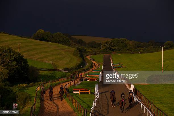 The first lot head up the polytrack under dark skies at Sandhill Racing Stables on September 30 2015 in Minehead England Sandhill Racing Stables set...