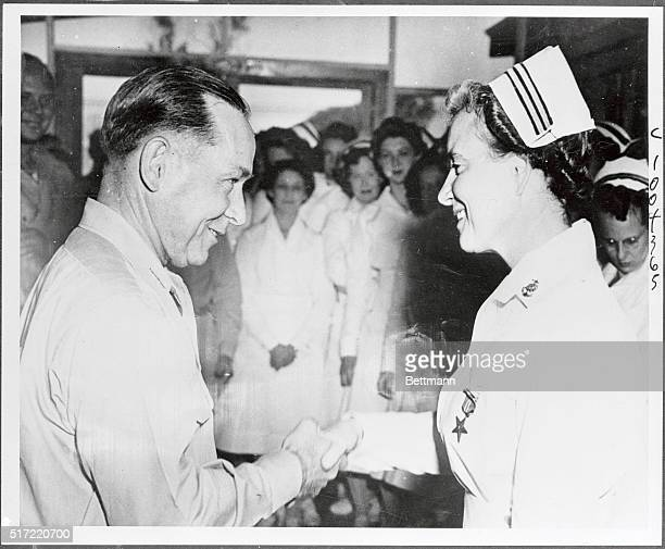 The first navy nurse to be presented with the bronze star medal Lieutenant Commander Faye E White USN receives a firm handshake from vice admiral...
