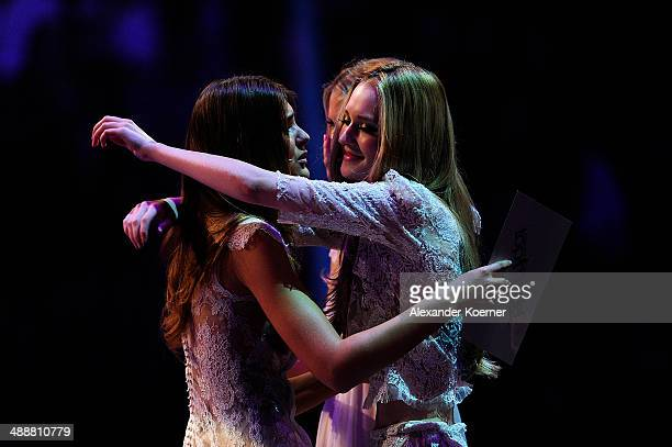 The first of three models Ivana Teklic cheers with model Stefanie Giesinger after being dismissed by the jury and presenter Heidi Klum during the...