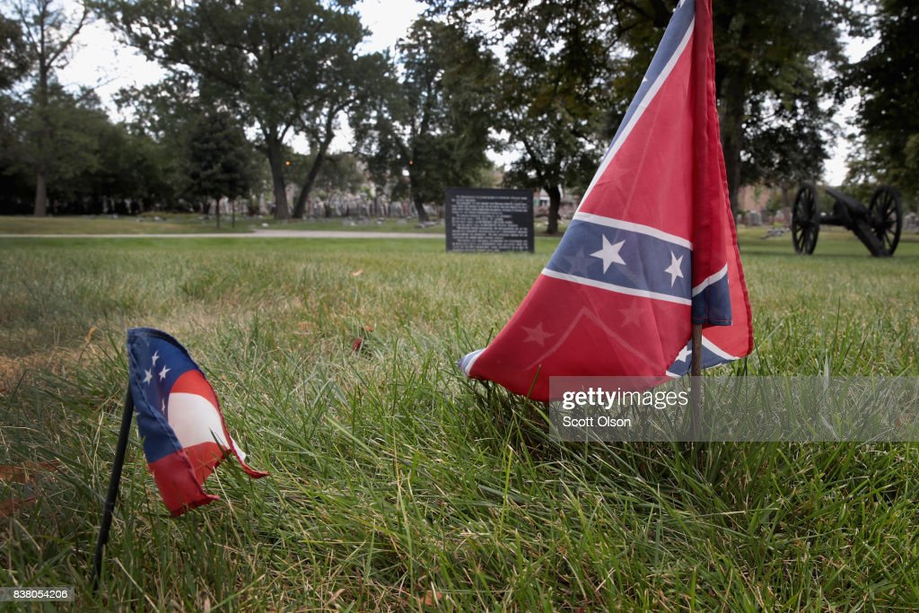 The first official flag of the Confederacy (L) and a Confederate Navy Jack flag sit at the base of Confederate Mound, a memorial to more than 4,000 Confederate prisoners of war who died in captivity at Camp Douglas and are buried around the monument, on August 23, 2017 in Chicago, Illinois. The monument, which is maintained by the National Park Service, is located inside the private Oak Woods Cemetery on Chicago's southside. The flags were removed by a National Park Service worker a short time after they were photographed. Cities around the country are debating what to do with Confederate monuments following recent protests and calls for their removal.