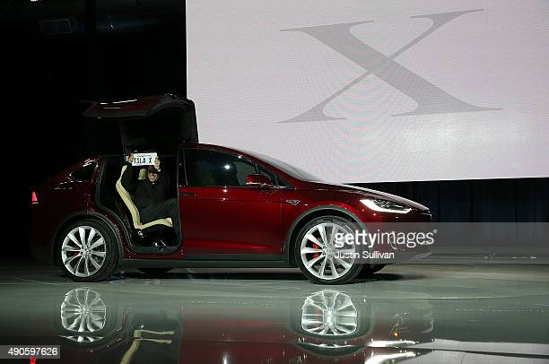 The first person to take delivery of the new Tesla Model X Crossover SUV holds up a vanity license plate as he gets into his new car for the first...