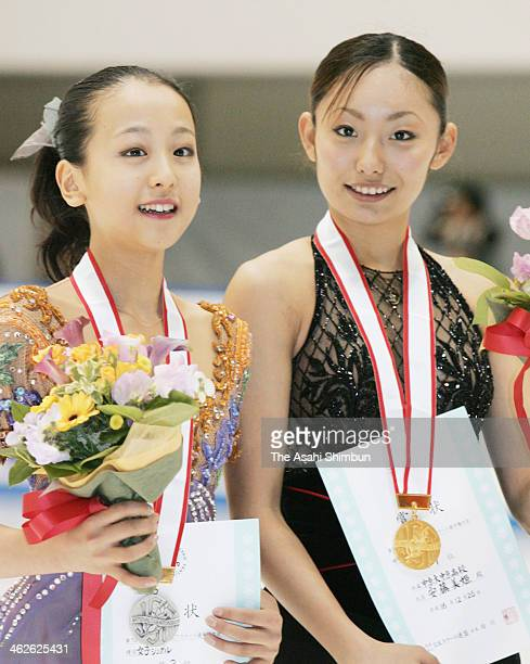 The first place winner Miki Ando and second place Mao Asada pose for photographs on the podium after their Ladies free proogram during All Japan...