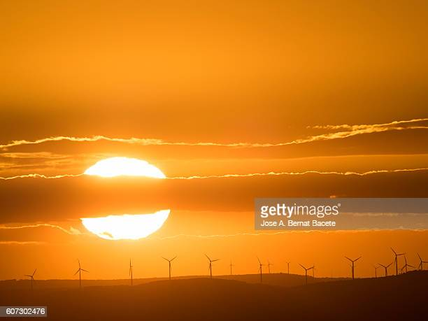 The first plane of a putting Sun, hiding between mountains with wind mills