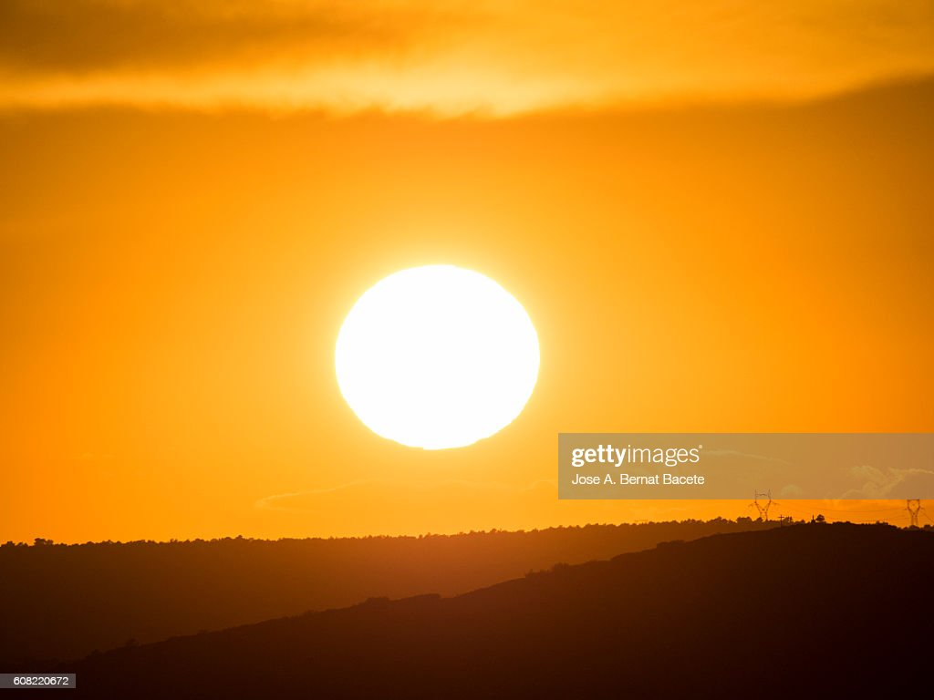 The first plane of a putting Sun, hiding between mountains with wind mills : Stock-Foto