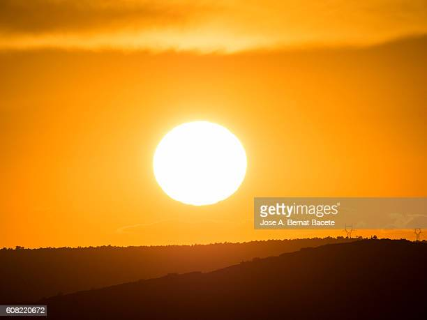 the first plane of a putting sun, hiding between mountains with wind mills - suns stock photos and pictures