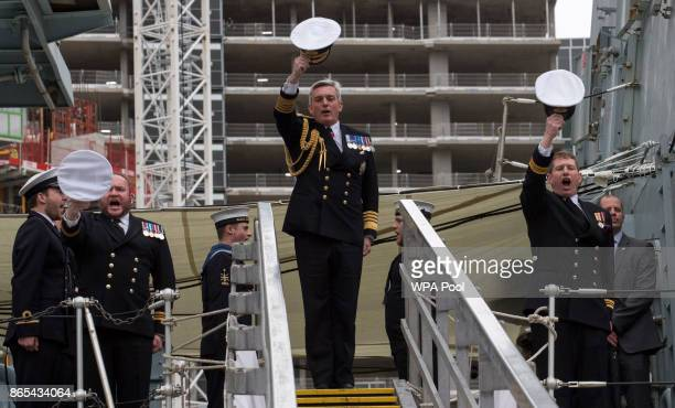 The First Sea Lord Admiral Sir Phillip Jones salutes Queen Elizabeth II as she visits HMS Sutherland in the West India Dock as the ship celebrates...