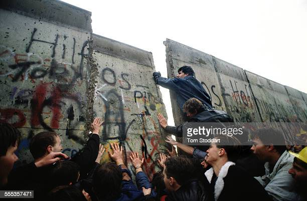 The first section of the Berlin Wall is pushed down by the hands of crowds of determined people on the morning of November 10 1989