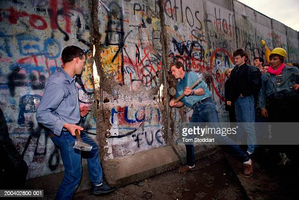 People watch as two men using sledgehammers hack at the the first section of the Berlin Wall to be torn down on the morning of November 10th 1989