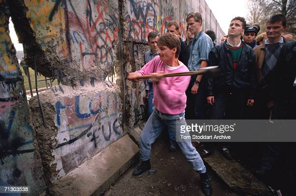 The first section of the Berlin Wall is torn down by crowds near the Brandenburg Gate on the morning of 10th November 1989 The area around the breach...
