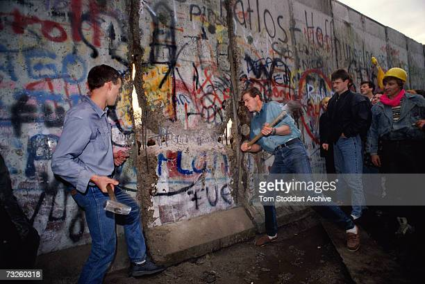 The first section of the Berlin Wall is torn down by crowds near the Brandenburg Gate on the morning of 10th November 1989. At centre, right is...