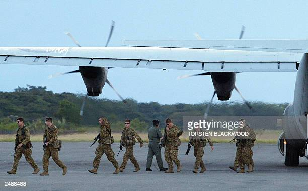 The first soldiers of the Australianled intervention force arrive after dawn for Operation Helpem Fren at Henderson Airport near Honiara 24 July 2003...
