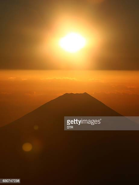 The first sunrise of the year of 2017 is seen in the east above Mount Fuji viewed onboard a special Japan Airlines flight to take in the view some...
