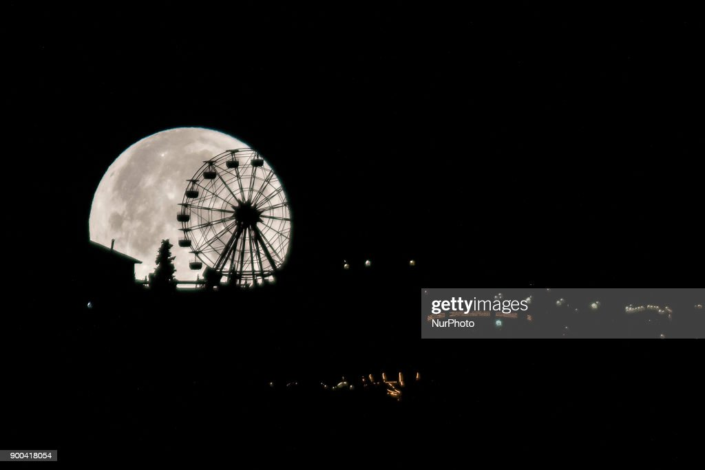 The first supermoon of 2018 is hidden behind the ferris wheel of the Tibidabo's theme park in Barcelona, Catalonia, Spain, on January 2, 2018