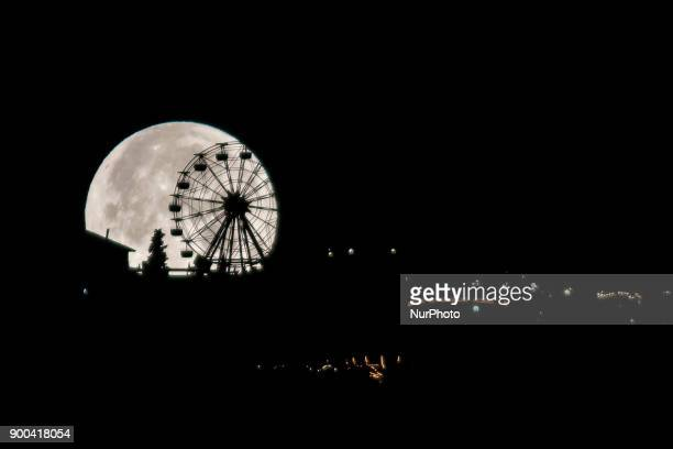 The first supermoon of 2018 is hidden behind the ferris wheel of the Tibidabo's theme park in Barcelona Catalonia Spain on January 2 2018